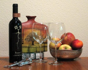 Still life photograph of a future painting with a bottle of Root 1: red wine, a pair of wine glasses, a silver bowl of fruit