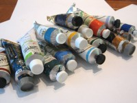 Scene of multiple tubes of oil paint on a work surface