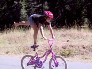This is a photo of a girl balancing on her bike seat with one leg while sticking her other leg straight out the back while holding her handlebars.