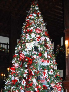 This is a photo of the famous Christmas tree in the lobby of the Hotel Del Coronado. It is at least twenty feet tall and heavily decorated with candy- and Christmas-themed ornaments and white lights.