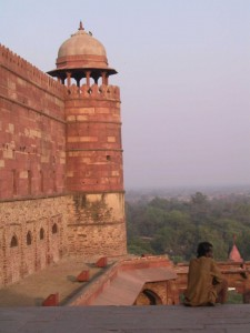 In this photo, an Indian man sits outside Fatehpur Sikri's red sandstone wall.