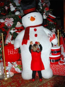 This is a photo of a toddler reaching up to pull on Frosty the Snowman's big red pom-pom buttons. Frosty is a six foot tall stuffed toy.