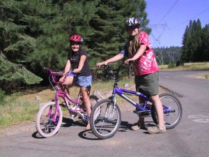 This is a photo of two girls on their bikes in Cool Springs Campground at Butt Lake Reservoir, Plumas County, CA.