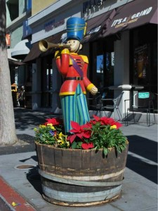 This is a photo of a wooden soldier blowing a trumpet in a flower barrel.
