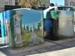 This is a photo of a utility box painted with an Italian motif to hide its plain and ugly exterior.