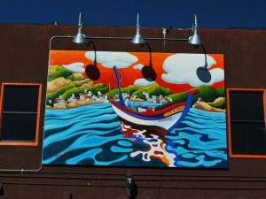 This is a photo of a large Italian themed image painted on a cafe building in Little Italy.