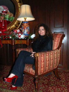 This is a photo of Tina Benino sitting in a chair in the lobby of the Hotel Del Coronado. The hotel is decorated for Christmas and everything is merry and bright. Including the visitors!