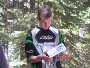 This is a photo of a teenage boy examining a box labeled River Rat Tube.