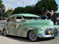 This is a photo of a mint green classic car that has been fully restored.