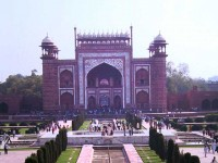 This is a photo of the view across the reflecting pool from the top deck of the Taj Mahal. It is a red sandstone building with typical Moghul architecture featuring domes, arches and minarets. The bas relief is white marble inlaid around the arches to define them.
